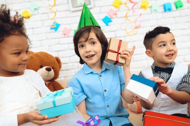 Menino tenta adivinhar isso na caixa de presente. Foto Premium