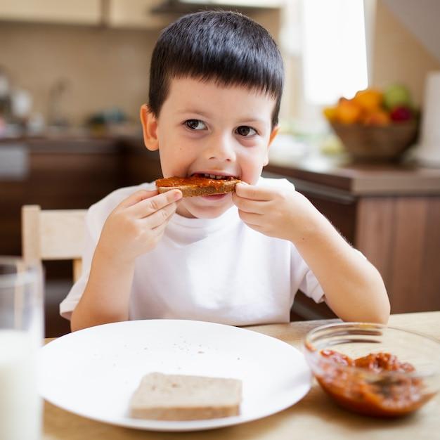 Menino tomando café da manhã em casa Foto gratuita
