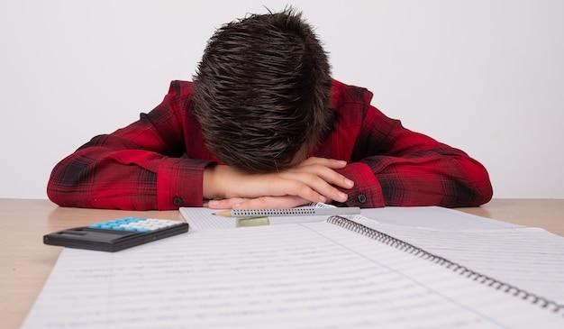 Menino triste com as mãos sobre a cabeça na mesa da escola Foto Premium