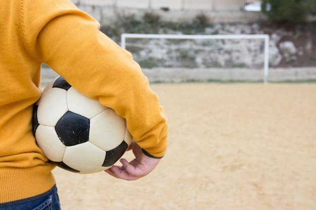 Menino triste, esperando para jogar bola em um campo de futebol velho Foto Premium