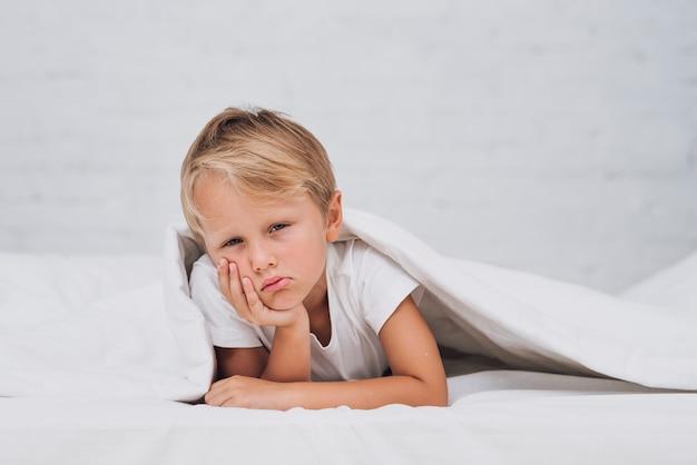 Menino triste, ficar na cama Foto gratuita