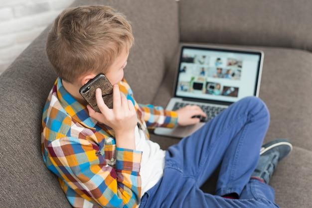 Menino, usando computador portátil, ligado, sofá, e, fazendo telefonema Foto gratuita