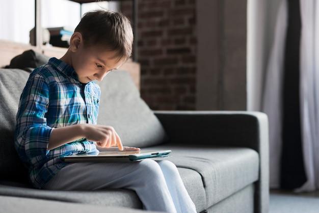 Menino usando o tablet no sofá Foto gratuita