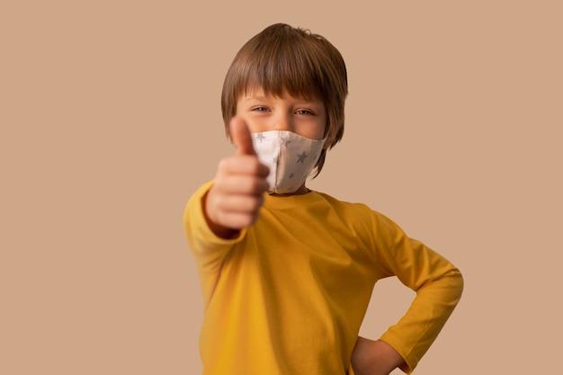 Menino usando uma máscara médica e mostrando o sinal de ok Foto gratuita