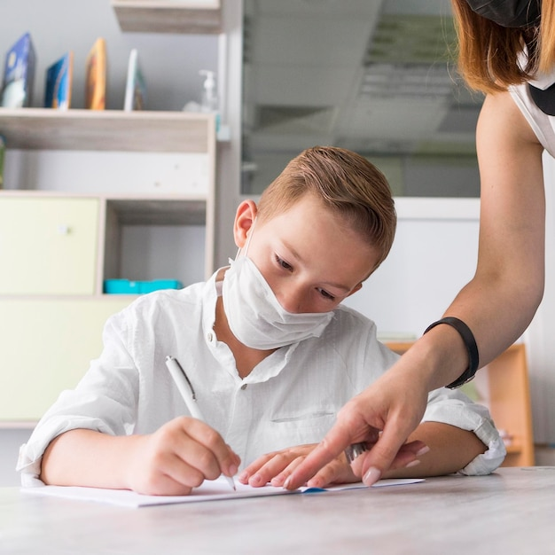 Menino usando uma máscara médica na sala de aula Foto gratuita