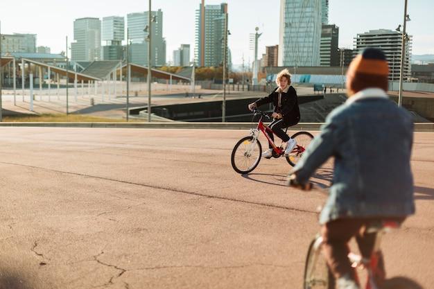 Meninos andando de bicicleta ao ar livre na cidade Foto gratuita