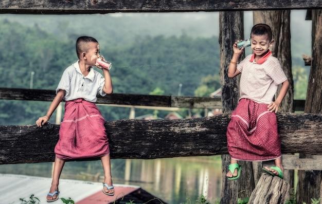 Meninos asiáticos que falam em um telefone da lata Foto Premium