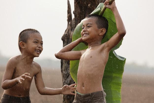Meninos asiáticos são felizes porque brincam na chuva. depois de uma longa seca Foto Premium