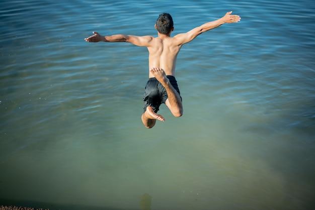 Meninos ativos que saltam dos registros na água. Foto gratuita