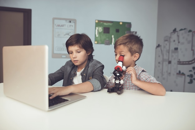 Meninos de assento que usam o portátil e o microscópio em casa. Foto Premium