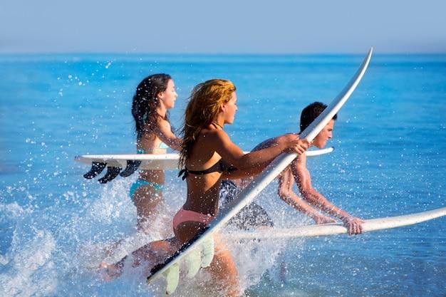 Meninos e meninas adolescentes surfistas correndo pulando na praia Foto Premium