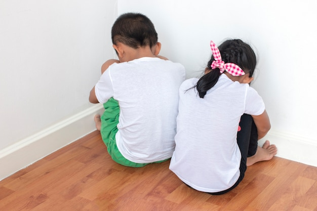 Meninos e meninas sentados em frente à parede no canto da sala Foto Premium