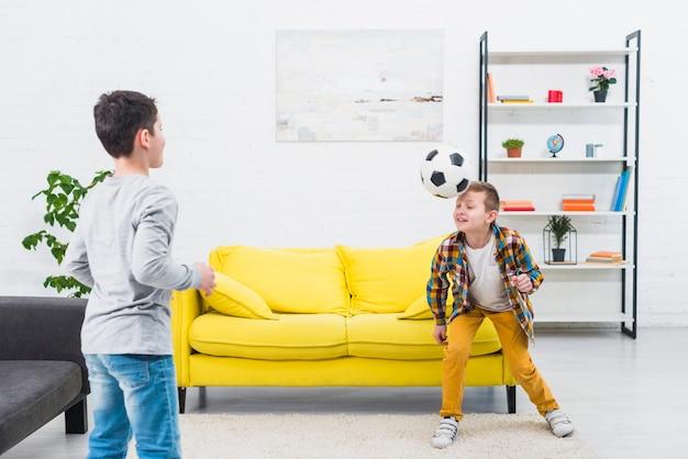 Meninos jogando futebol na sala de estar Foto gratuita