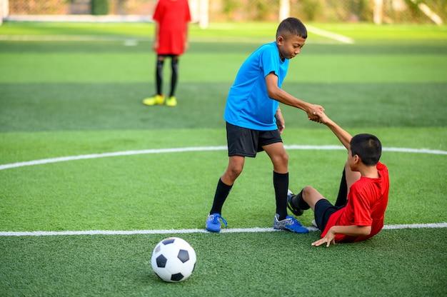 Meninos jogando futebol no campo de treino de futebol Foto Premium