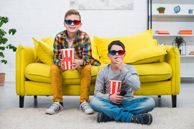 Meninos no sofá com óculos 3d Foto gratuita