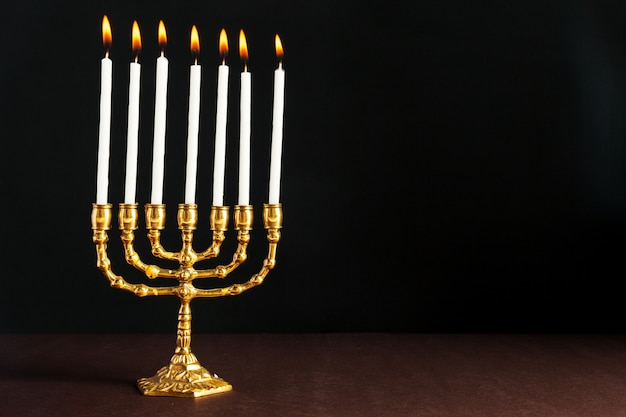 Menorá de bronze de hanukkah com velas acesas Foto Premium