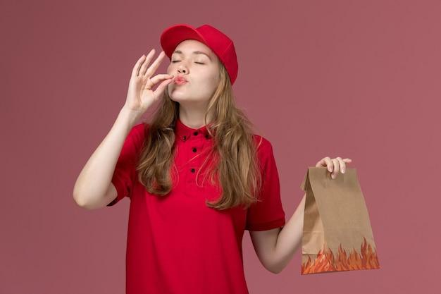 Mensageira de uniforme vermelho segurando pacote de comida de papel na rosa, entrega de serviço de trabalhador uniforme de trabalho Foto gratuita