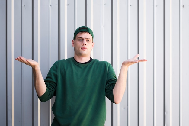 Mensageiro jovem incompreensível com as mãos levantadas Foto gratuita
