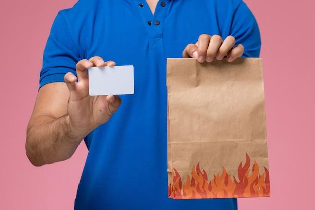 Mensageiro masculino de uniforme azul segurando um pacote de comida e cartão na rosa, entrega de trabalho de serviço uniforme Foto gratuita