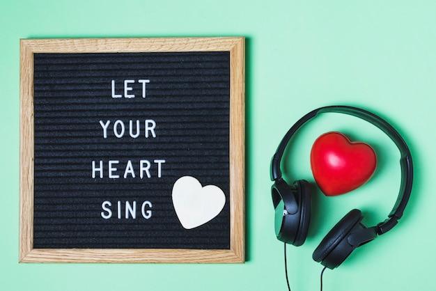 Mensagem a bordo; coração vermelho e fone de ouvido sobre fundo verde Foto gratuita