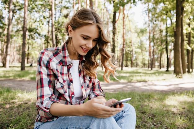 Mensagem de mensagens de texto curiosa garota encaracolada enquanto está sentado na grama. foto ao ar livre da magnífica senhora elegante relaxando na floresta. Foto gratuita