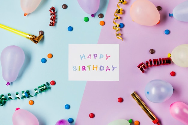 Mensagem do feliz aniversario no azul e no rosa cercados com flâmulas; pedras preciosas e balões em pano de fundo colorido Foto gratuita
