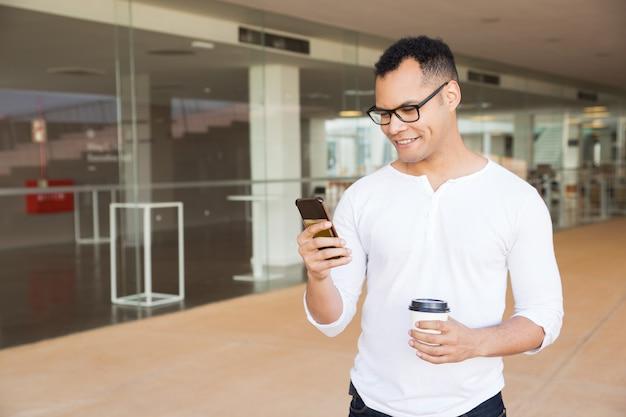 Mensagens de homem sorridente no telefone, segurando o café para viagem Foto gratuita