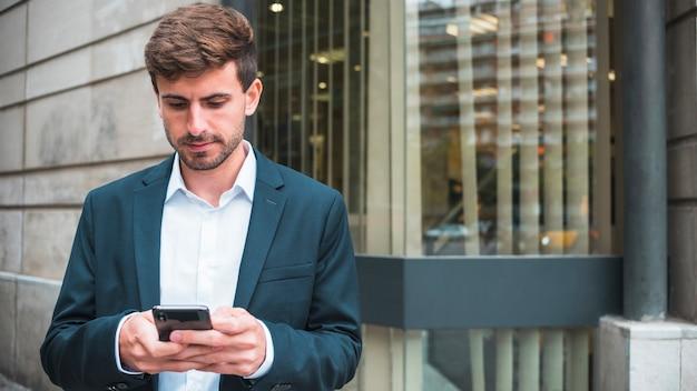 Mensagens de jovem empresário no smartphone Foto gratuita