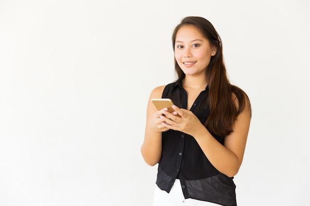 Mensagens de mulher pelo smartphone e sorrindo para a câmera Foto gratuita