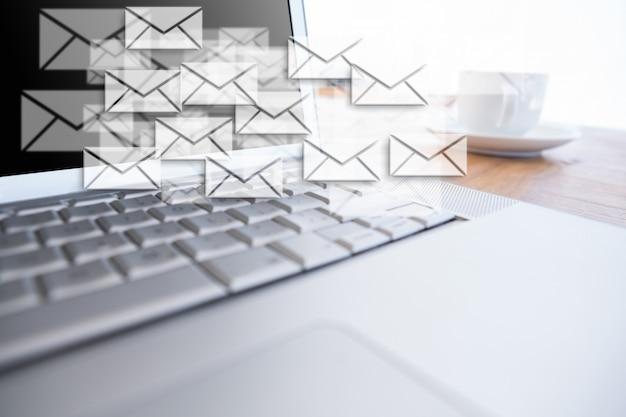 Mensagens que flutuam ao lado de um laptop Foto gratuita