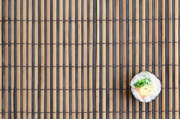 Mentira de rolo de sushi em um fundo de esteira serwing palha de bambu Foto Premium