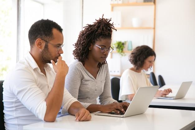 Mentor assistindo estagiário trabalhando no computador Foto gratuita