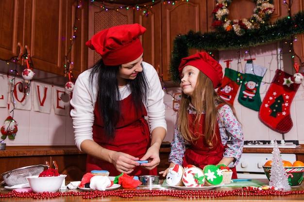 Menu de jantar de festa de natal idéia de sobremesa cupcakes de chocolate com menta creme de leite polvilhar decoração mãe filha ano novo avental vermelho chef chefe confeiteiro Foto Premium
