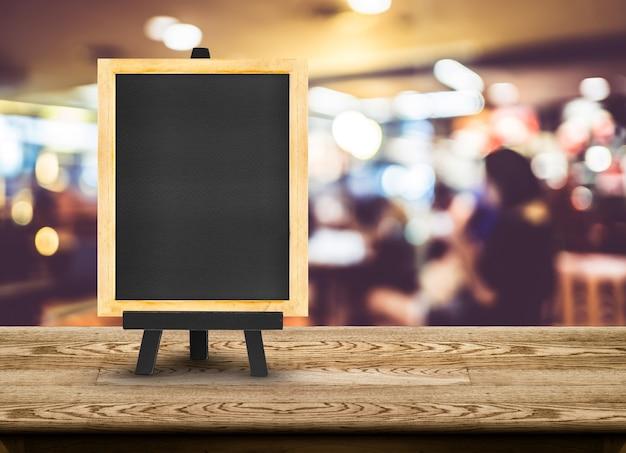 Menu de quadro-negro com cavalete na mesa de madeira com fundo de restaurante borrão Foto Premium