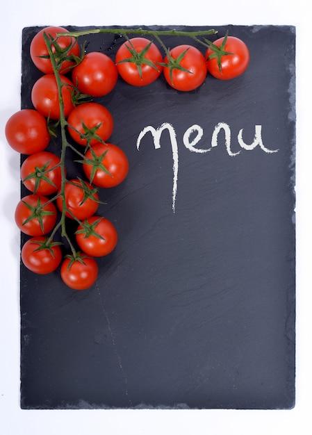 Menu em um quadro negro com tomates Foto Premium