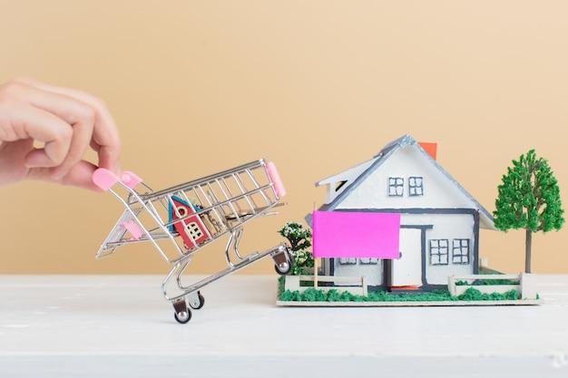 Mercado imobiliário, casa no carrinho de compras Foto gratuita