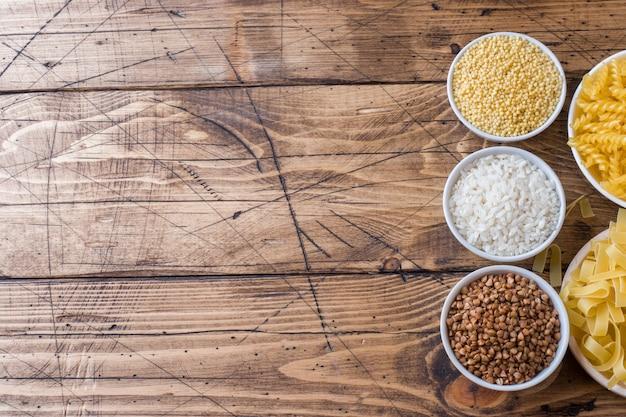 Mercearia de cereais secos. arroz macarrão de trigo sarraceno e milho na mesa de madeira. Foto Premium