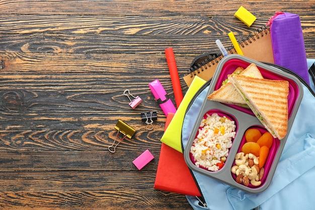 Merenda escolar, mochila e artigos de papelaria com fundo de madeira Foto Premium