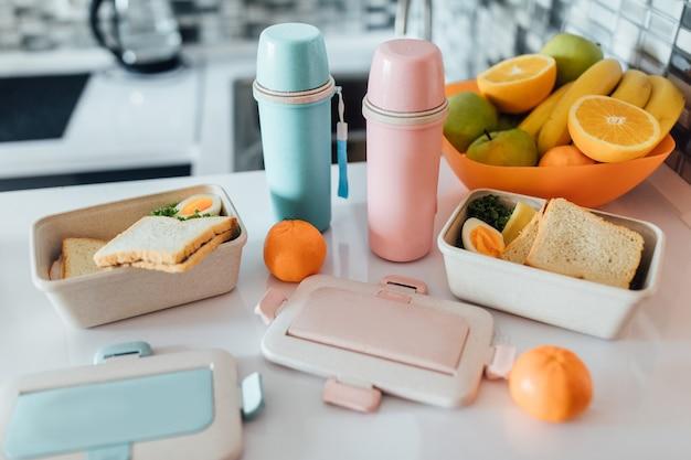 Merendeira cheia de sanduíches perto de duas garrafas térmicas, maçãs e laranjas frescas, bananas em frente à moderna mesa branca da cozinha Foto Premium