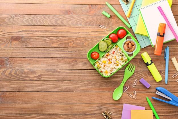 Merendeira escolar com comida saborosa e artigos de papelaria com fundo de madeira Foto Premium