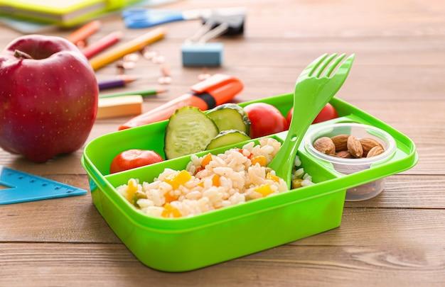 Merendeira escolar com comida saborosa em fundo de madeira Foto Premium