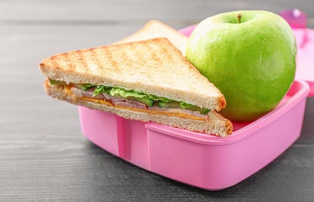 Merendeira escolar com comida saborosa em madeira Foto Premium