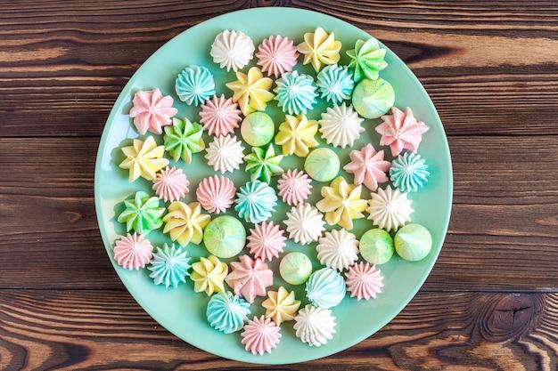 Merengues coloridos em um prato na madeira Foto Premium