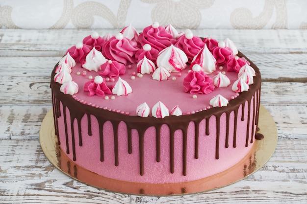 Merengues de bolo de creme-de-rosa com manchas de chocolate em um fundo branco de madeira Foto Premium