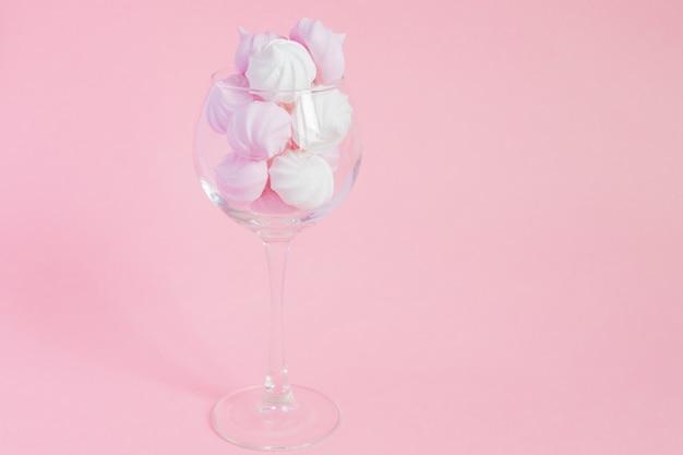 Merengues torcidos brancos e rosa em um copo de videira em rosa Foto Premium