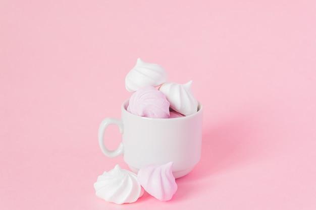 Merengues torcidos brancos e rosa em uma xícara de café de porcelana pequena em fundo rosa. sobremesa francesa preparada a partir de chantilly com açúcar e claras de ovos cozidas. cartão com espaço de cópia Foto Premium