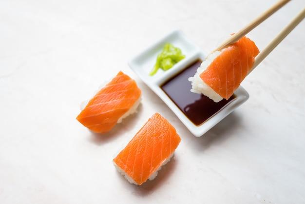 Mergulhando sushi de salmão em molho de soja Foto Premium