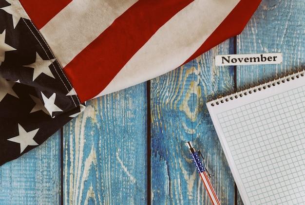 Mês de novembro do ano civil estados unidos da américa bandeira do símbolo da liberdade e da democracia com o bloco de notas em branco e caneta na mesa de escritório de madeira Foto Premium