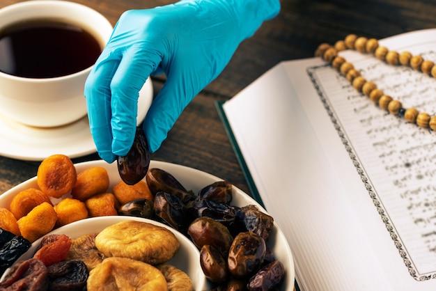 Mês sagrado do ramadã, closeup mãos em luvas médicas tirar datas, conceito iftar, livro do alcorão, rosário de madeira, xícara de chá, quarentena Foto Premium