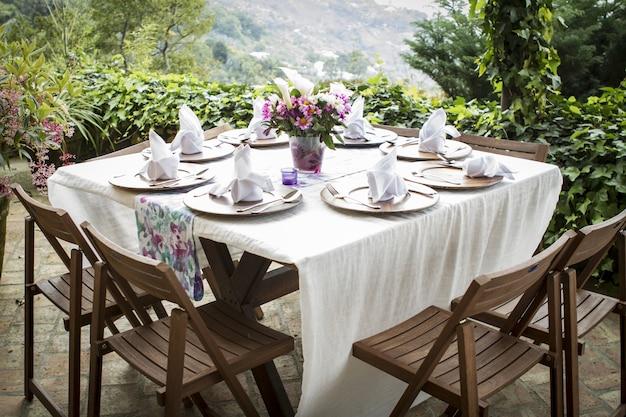 Mesa cheia de pratos e um vaso de flores em uma bela varanda com uma vista incrível Foto gratuita
